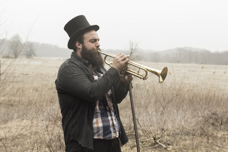 Stylish bearded gypsy plays trumpet on a wilderness path photo