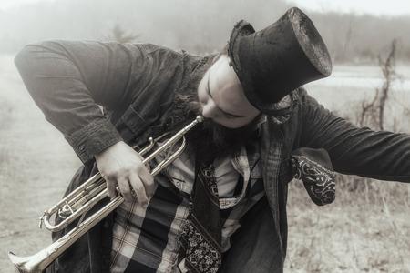 vagabond: Stylish bearded gypsy plays trumpet on a wilderness path Stock Photo