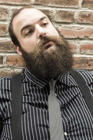 Well dressed bearded man ponders life against textured brick wall background