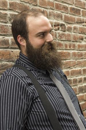 bärtiger mann: Gut gekleideter b�rtiger Mann starrt einen finsteren Blick gegen texturierte Mauer Hintergrund Lizenzfreie Bilder