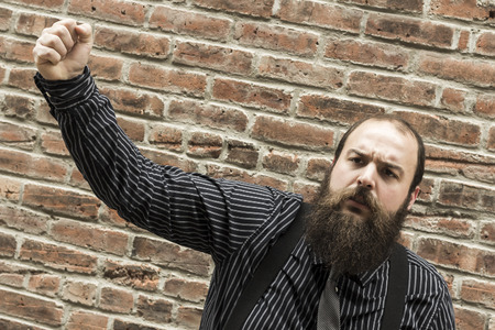 disgruntled: Well dressed bearded man raises his fist in dismay