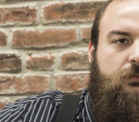 hombre con barba: Hombre barbudo Elegante reflexiona sobre la vida contra el fondo de pared de ladrillo con textura