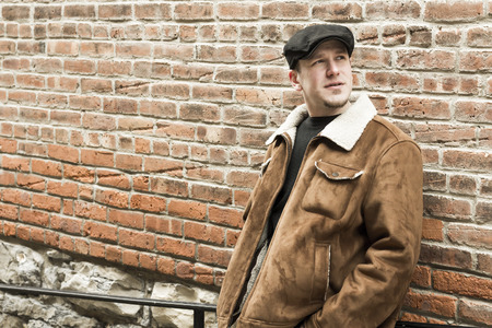 early 30s: Cool guy rocks an aviator jacket and newsboy cap as he takes a moment to think