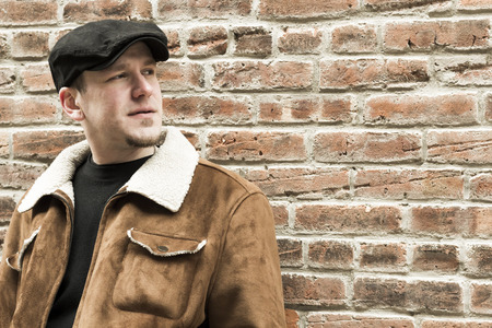 loitering: Cool guy rocks an aviator jacket and newsboy cap as he takes a moment to think