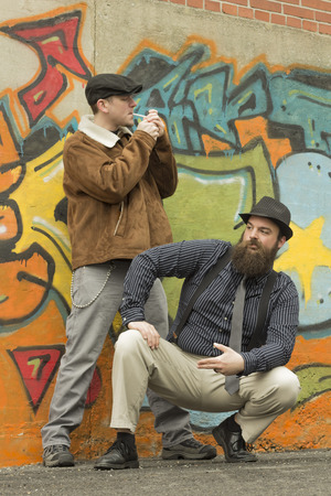 newsboy cap: Two snazzy stylish men hang out on a street corner