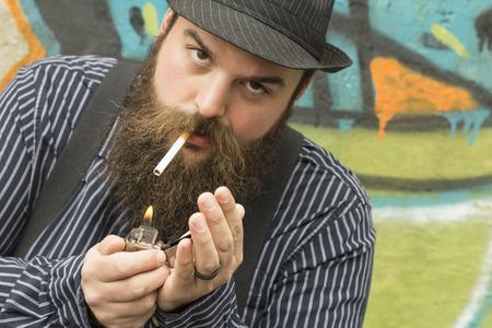 hombre con barba: Hombre barbudo Snazzy enciende un cigarrillo en una calle de la ciudad Foto de archivo