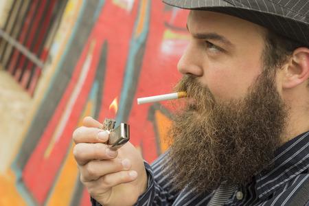 bärtiger mann: Snazzy b�rtiger Mann z�ndet sich eine Zigarette auf einer Stadtstra�e Lizenzfreie Bilder