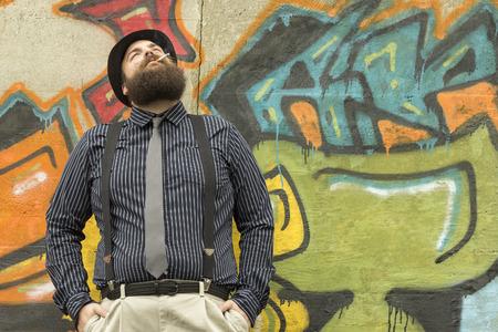 hombre con barba: Hombre barbudo Snazzy fuma un cigarrillo en una calle de la ciudad