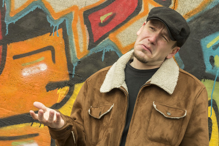 Cool guy rocks an aviator jacket and newsboy cap as he weighs his options Stock Photo