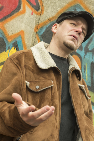 newsboy cap: Cool guy rocks an aviator jacket and newsboy cap as he weighs his options Stock Photo