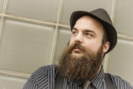 bärtiger mann: Gut gekleidet gl�cklicher b�rtiger Mann sitzt vor einem Glasgeb�ude