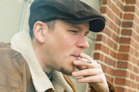 cool guy: Cool guy in aviator jacket and newsie cap relaxes against a glass wall and enjoys his cigarette