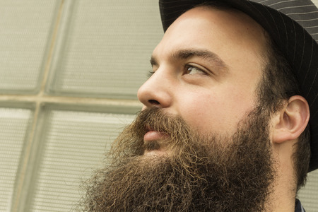 hombre con barba: Hombre barbudo feliz Elegante sienta contra un edificio de cristal