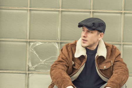 newsboy cap: Cool guy in aviator jacket and newsie cap relaxes against a glass wall Stock Photo