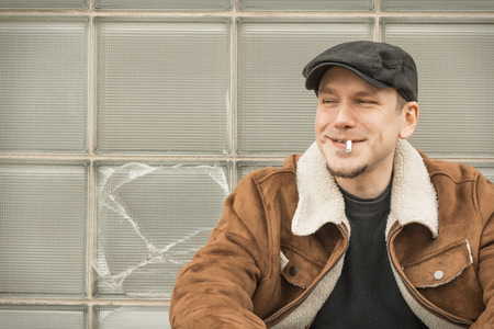 loitering: Cool guy in aviator jacket and newsie cap relaxes against a glass wall as he smiles a silly grin