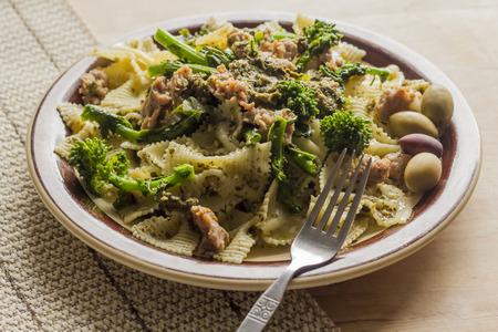 comida: Bowtie pasta pesto com salsicha solo e rabe brócolos decorado com azeitonas fantasia