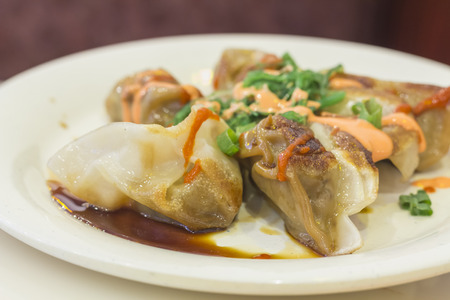 Fancy szechuan dumplings topped with sriracha hot sauce spicy mayonnaise and seaweed salad