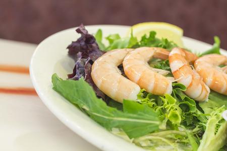 shrimp cocktail: Shrimp cocktail salad with legs on shrimp and lemon wedge Stock Photo