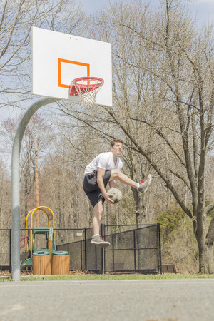layup: Young man doing basketball trick shots as he leaps through the air
