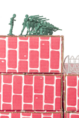 green plastic soldiers: Green army men guarding the top of red cardboard brick base