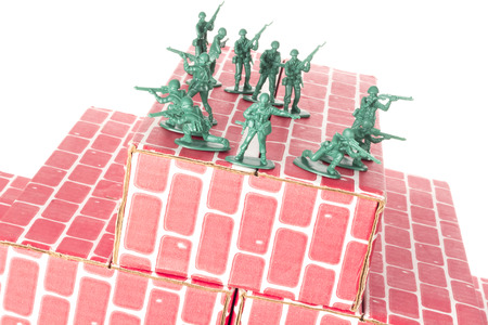 guarding: Green army men guarding the top of red cardboard brick base