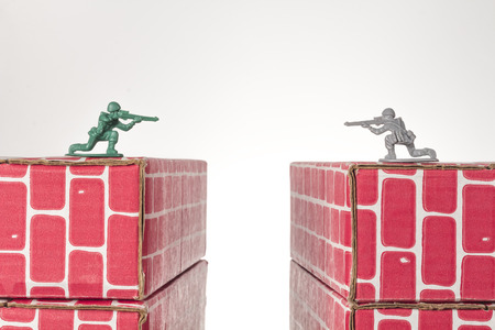green plastic soldiers: Rival toy army men aim guns at eachother atop opposing toy bricks
