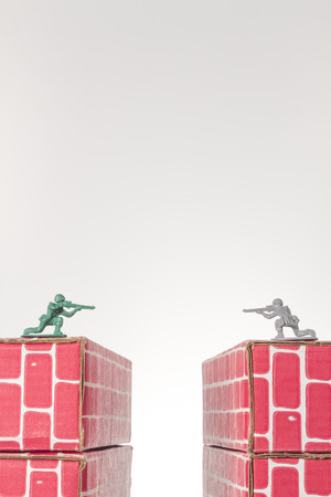 rival: Rival toy army men aim guns at eachother atop opposing toy bricks