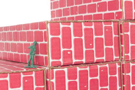 banging: Green army man banging head against a brick wall Stock Photo