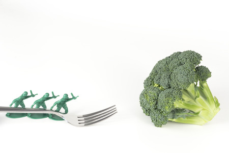 green plastic soldiers: Army Men carry fork to broccoli in childrens healthy eating image
