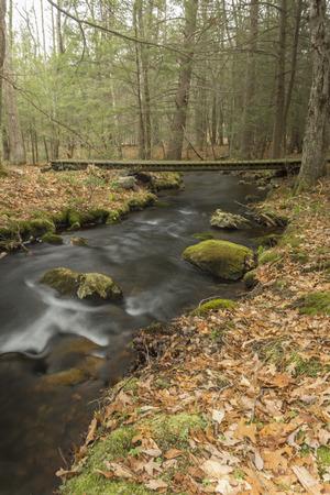 wooden bridge: Misty river rapids run under a wooden bridge Stock Photo