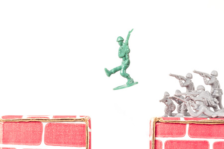 Green army man jumps ravine to escape gray army photo
