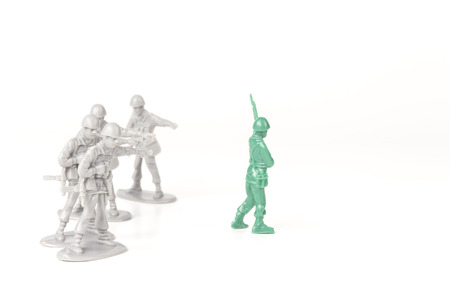 peer pressure: Gray toy soldiers pointing and bullying a green toy soldier