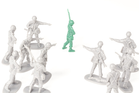 green military miniature: Gray toy soldiers pointing and bullying a green toy soldier