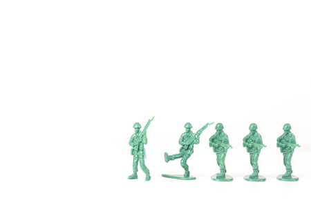 green military miniature: Green army leader steps off his foot stand and others follow Stock Photo