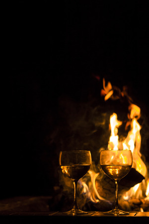 Two wineglasses by the campfire in this picturesque romantic scene Stok Fotoğraf