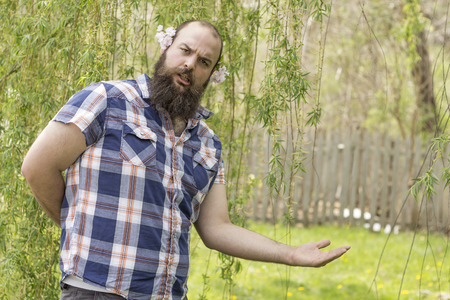 motioning: Flowers behind the ears of this bearded man posing for the camera Stock Photo