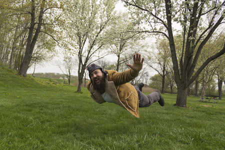 Bearded aviator soars through the air like an airplane Stock Photo