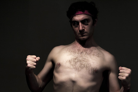 feeble: Very skinny headband wearing fighter shows skills Stock Photo