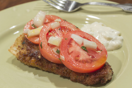 Breaded cod fillet with tomato and onion with tartar sauce Stock Photo