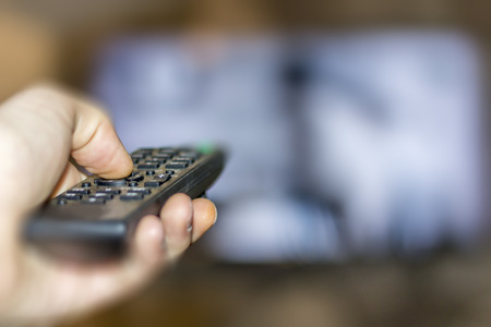 big screen tv: Close up of remote in hand with shallow depth of field during television watching Stock Photo