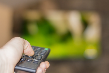 Close up of remote in hand with shallow depth of field during television watching Stok Fotoğraf