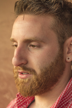 pierced ears: Portrait of bearded young man with gauged ears and stylish hair