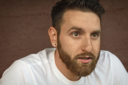 raised eyebrow: Portrait of bearded young man with gauged ears and stylish hair