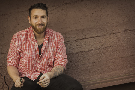 chuckle: Portrait of bearded young man with gauged ears and stylish hair