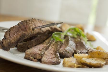 Sliced juicy skirt steak with potatoes and arugula garnish Imagens