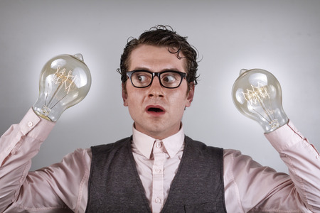 semi dress: Nerdy four eyed businessman is shocked by his lightbulb hands