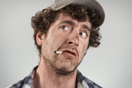 redneck: Scared redneck cowardly smoke a cigarette and searches for danger Stock Photo