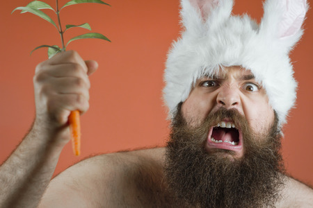 Angry bearded man wearing bunny ears waves carrot to attack
