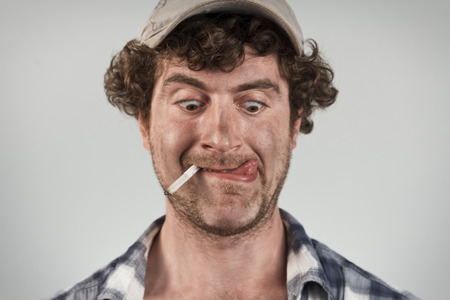 redneck: Hungry redneck licks his lips while smoking a cigarette Stock Photo