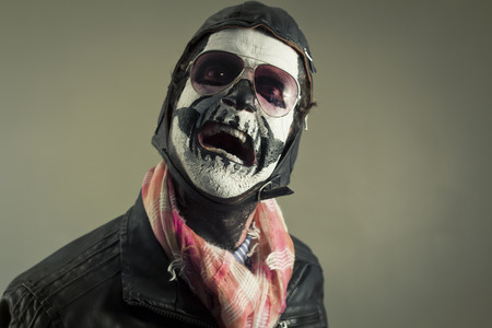 Scared aviator with face painted as human skull Imagens